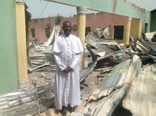 BISHOP OLIVER IN INSPECTING A BURNT CHURCH IN BAHULI
