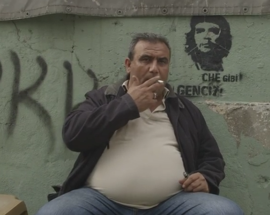 Screen shot a man sits in front of PKK grafiti: Note who the picture is next to this man:  Che Guevera