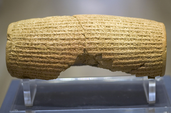 Rear view of a barrel-shaped clay cylinder resting on a stand. The cylinder is covered with lines of cuneiform text wikimedia commons