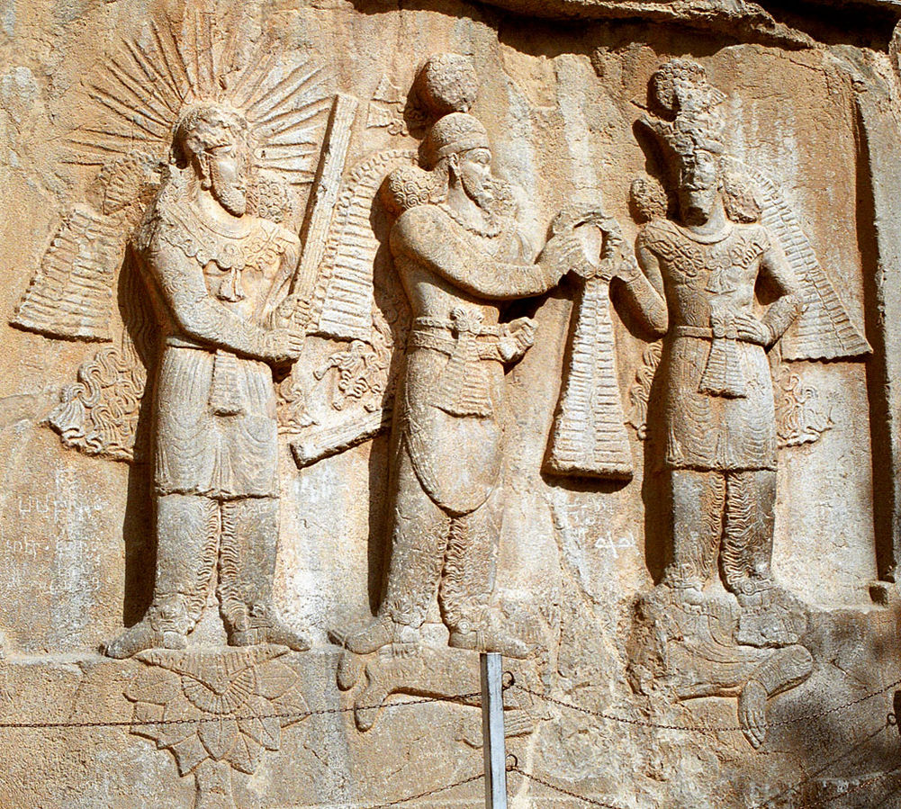 Taq-e Bostan: high-relief of Ardeshir II investiture; from left to right: Mithra, Shapur II, Ahura Mazda. Lying down: dead Roman emperor Julian.(Wikimedia commons)